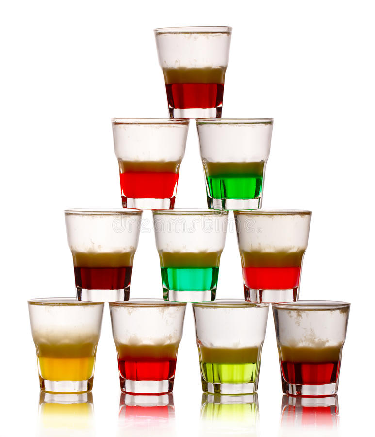 Pyramid of short colored alcohol cocktails isolated on white. Background royalty free stock photo