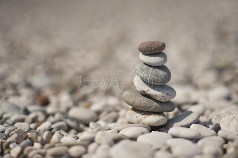 A pyramid of stacked flat pebble stones 8646. The pyramid of pebbles on the beach stock photo