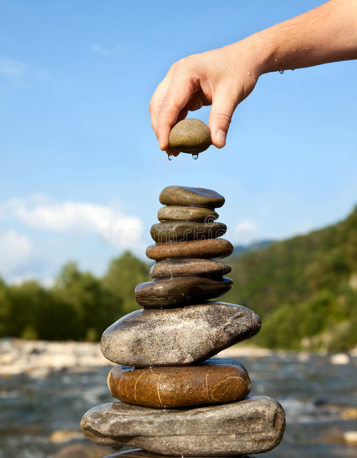 Pyramid of stones. Man's hand puts Pyramid of stones stock photography