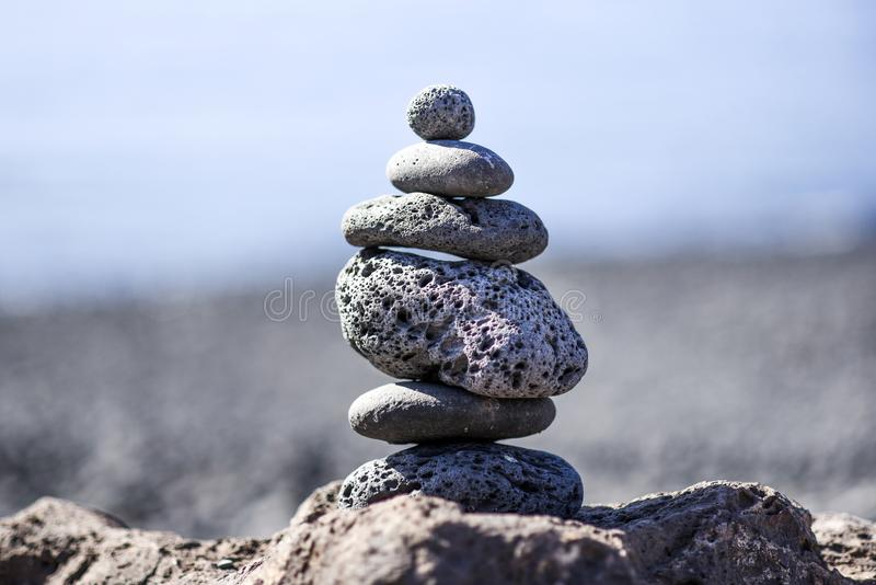 Pyramid of stones arranged from volcanic stones on the beach at royalty free stock image