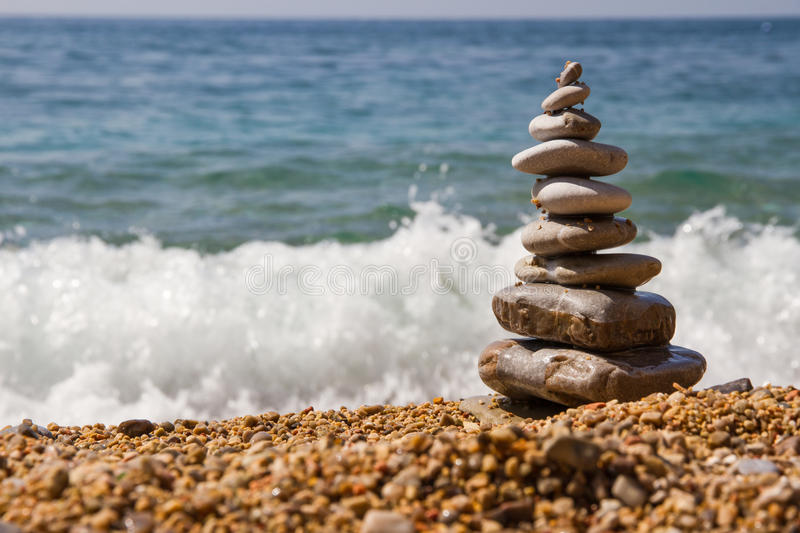 Pyramid from stones. Pyramid of stones on a background of sea waves stock photo