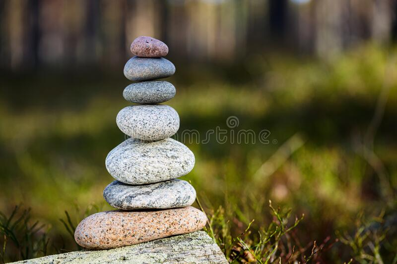 Pyramid stones balance on a stump in the forest. The object is in focus, the background is blurred royalty free stock photo