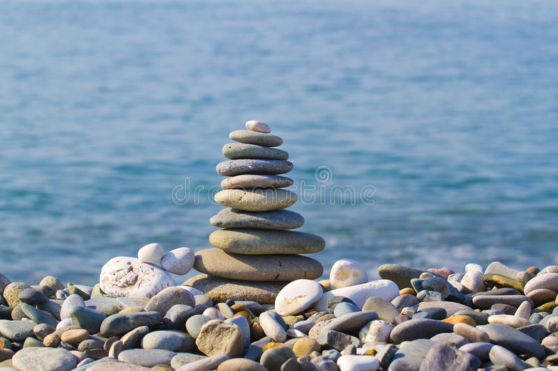 Pyramid of stones on the beach royalty free stock photo