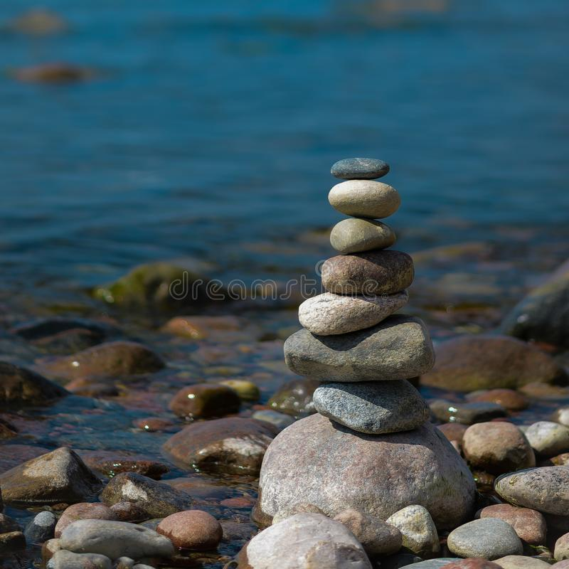 Pyramid of stones in the evening.On the sea shore a pyramid of stones. Dream on the beach stock photo