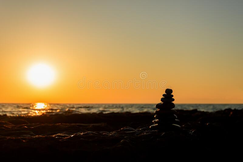 Pyramid of stones for meditation, lying on the sea coast at sunset, against the sun. stock image