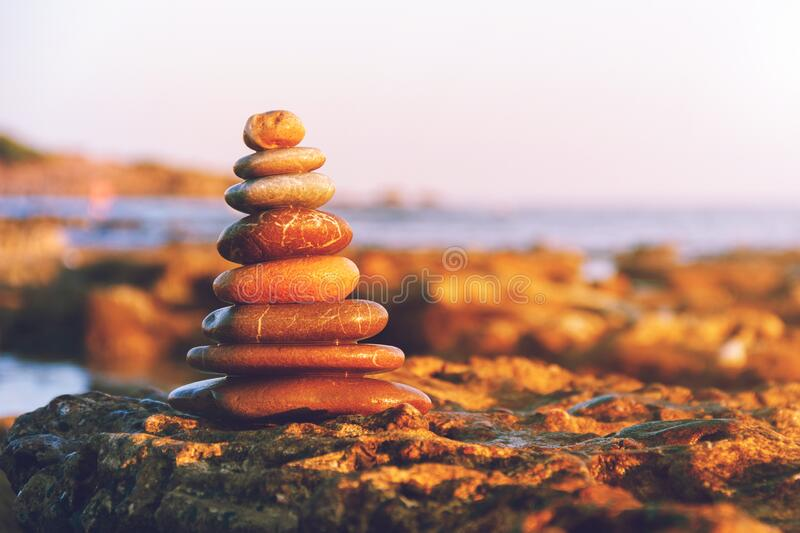 Pyramid of stones for meditation lying on sea coast. Zen stones sunset sea peace of mind concept. stock images