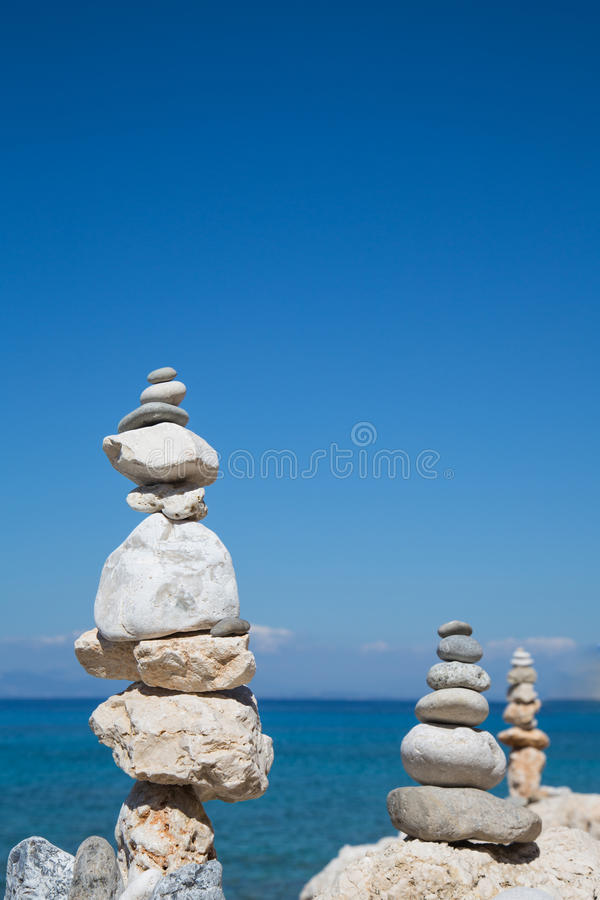 Pyramid of stones at the ocean. Blue water background. royalty free stock photos
