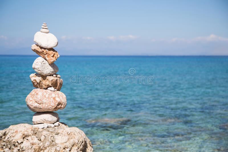 Pyramid of stones at the ocean. Blue water background. Pyramid of stones at the ocean. Blue water background in summertime stock photos