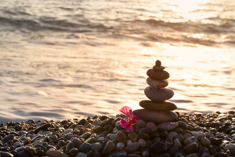 Pyramid of stones and red flower on the seashore. Pyramid of stones and a red flower on the seashore at sunset. Seascape. The concept of balance and spirituality stock photo