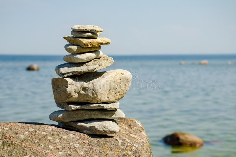 Pyramid of stones on the shore of the blue sea. royalty free stock photography