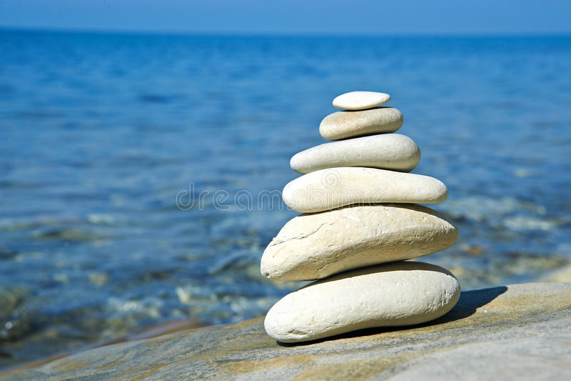 Pyramid of stones zen balance in sea shore stock images