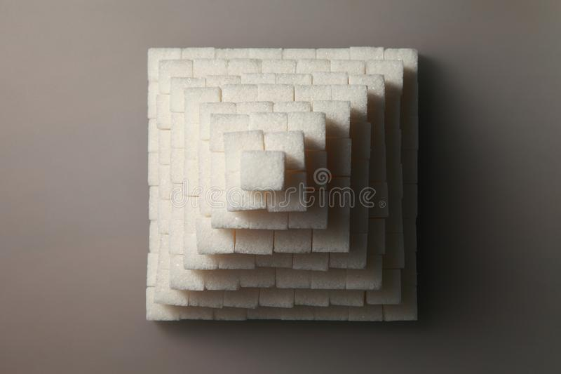 Pyramid from sugar cubes, on a gray background. Removed from the top view. With the entrance from the front. Removed from the bottom view stock photography