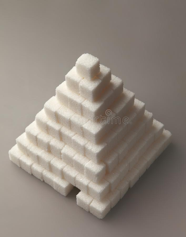 Pyramid from sugar cubes, on a gray background. Removed from the top view. royalty free stock photography