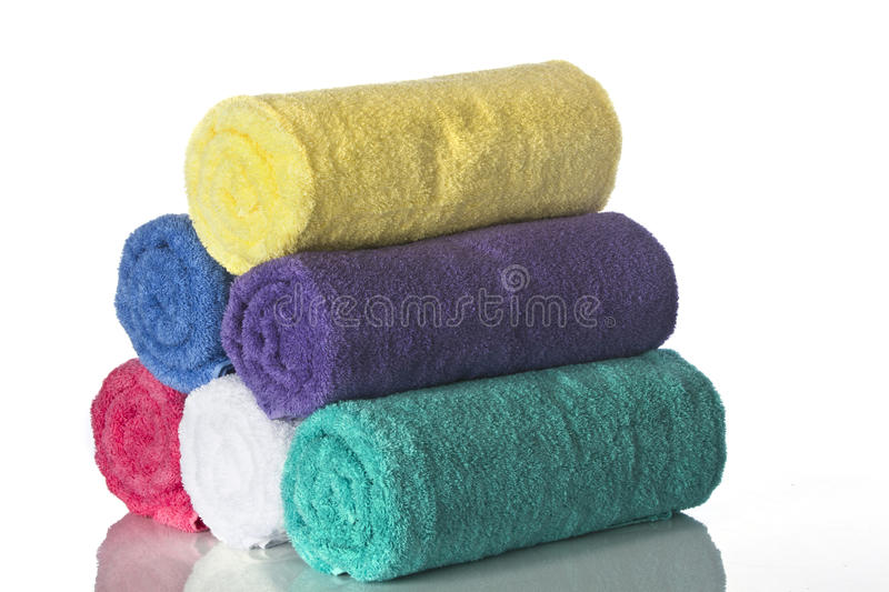 Pyramid of Towels. Colored towels rolled and stacked in a pyramid shape against a white backdrop in a studio setting stock photography