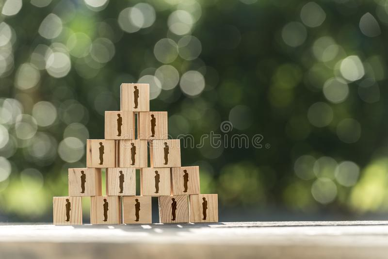Pyramid of toy wooden blocks with human icons. Of a businessman conceptual of management structure, human resources, business hierarchy, teamwork and employees stock images