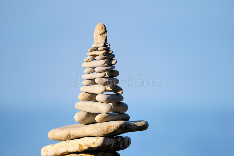 Pyramid of white stones. Balancing of white pebbles each other on the seacoast stock image