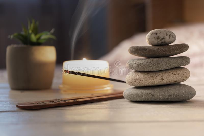 Pyramid of zen stones, burning candle, incense stick, bedroom interior. Evening meditation concept. stock photography