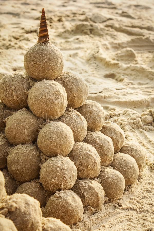 Sandcastle with seashell on the beach royalty free stock photo