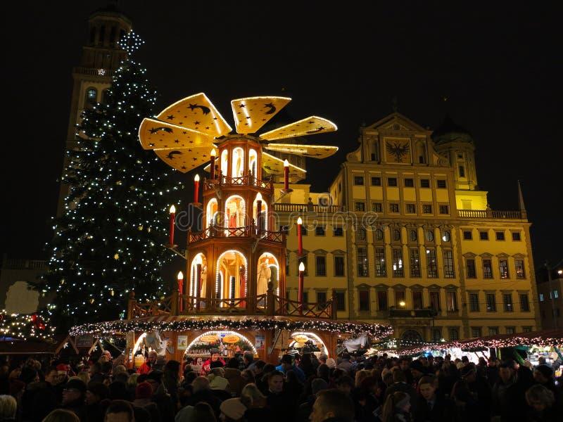 Pyramide, arbre et personnes de Noël au marché par nuit photos stock