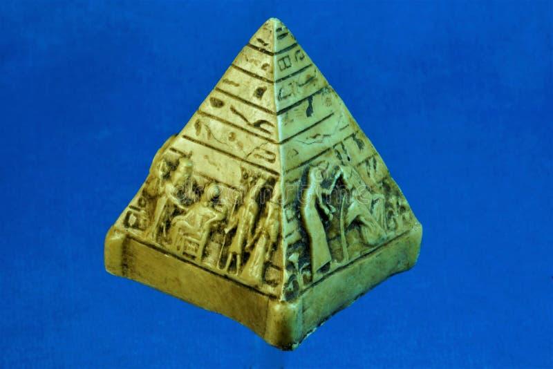 Pyramide de souvenir de figurine de l'Egypte sur un fond bleu photos stock