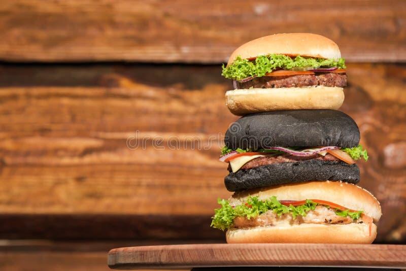 Pyramide de trois hamburgers sur un conseil en bois et un fond photos stock