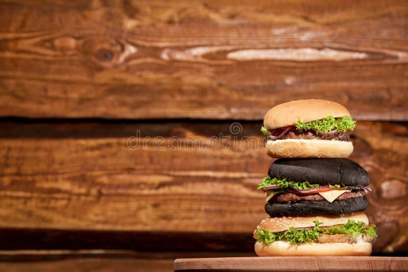 Pyramide de trois hamburgers de viande fraîche placés sur un fond en bois images stock