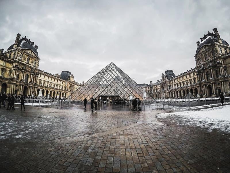 Pyramide du Louvre besichtigt von den Touristen und von Musee du Louv stockbild