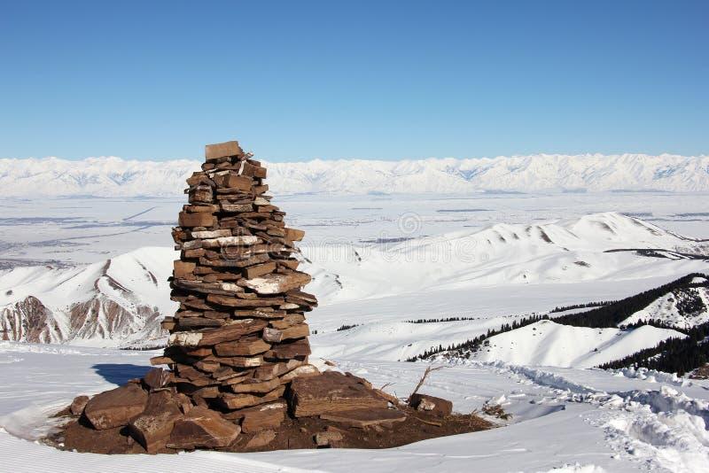 Pyramide en pierre sur le dessus de la montagne, vue sur le lac Issyk Kul val image libre de droits