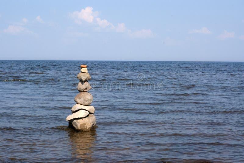 Pyramide von den Steinen, die im Wasser auf der Küste von Estland stehen stockbilder
