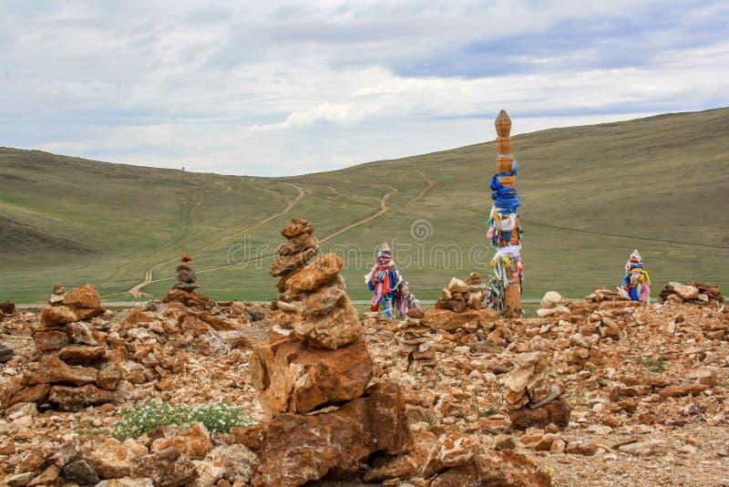 Pyramiden von Steinen und eine religiöse Säule gebunden mit bunten Bändern stockfoto