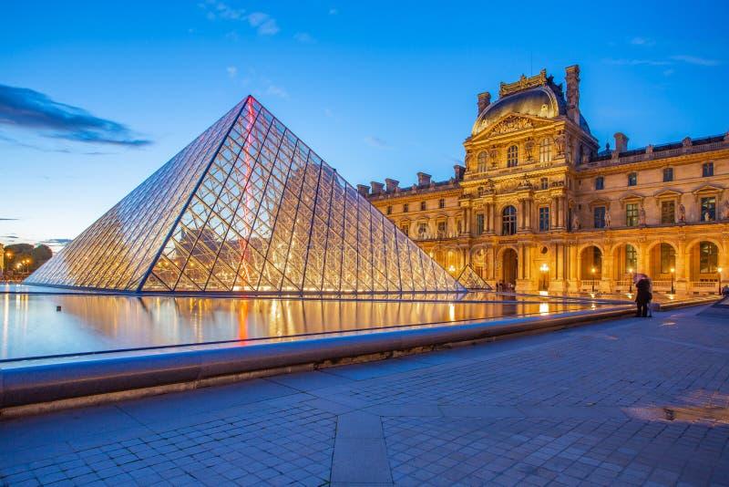 Pyramidexponeringsglas med sikt av Louvremuseet på natten i Paris arkivfoton