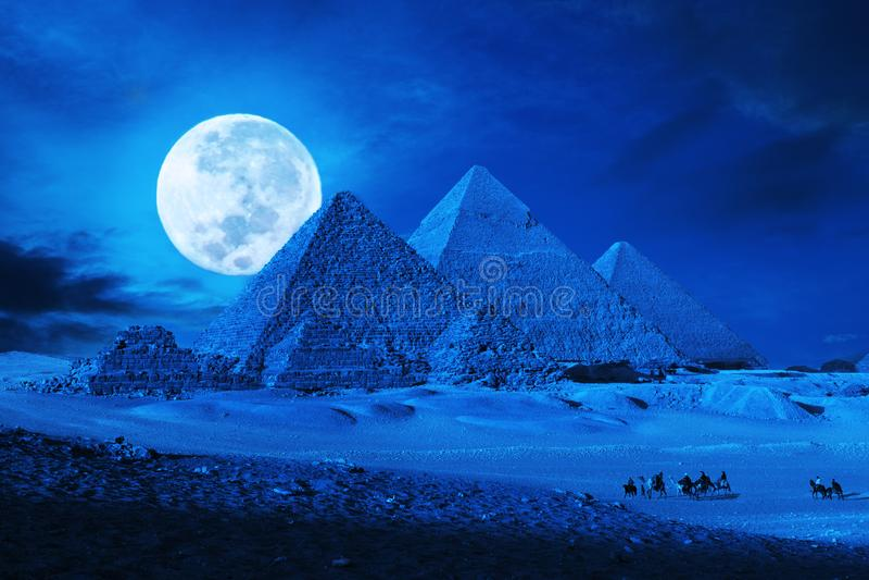 Pyramids giza cairo egypt with camel train,caravane at full moon lit night phantasy. Wide shot of pyramids at moon lit night, with light rays and Camel Train royalty free stock photography