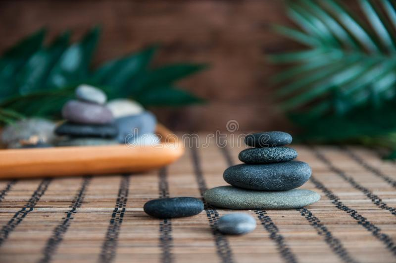 Pyramids of gray zen stones with green leaves and Buddha statue. Concept of harmony, balance and meditation, spa, massage, relax stock photos