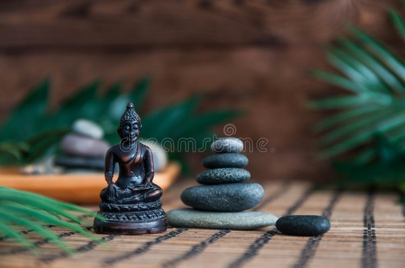 Pyramids of gray zen stones with green leaves and Buddha statue. Concept of harmony, balance and meditation, spa, massage, relax royalty free stock photography