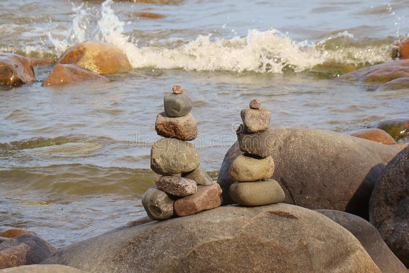 Pyramids of stones laid out on the shore of a rocky beach stock image