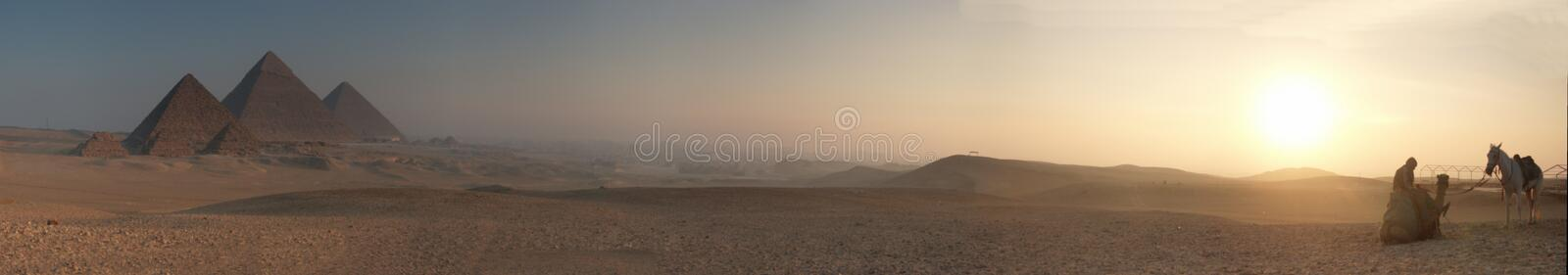 Pyramids sunrise blur 5000x878. Picture made during sunrise on the Gizeh plateau. The guide with horse and cemal on the right. The Pyramids on the left royalty free stock images
