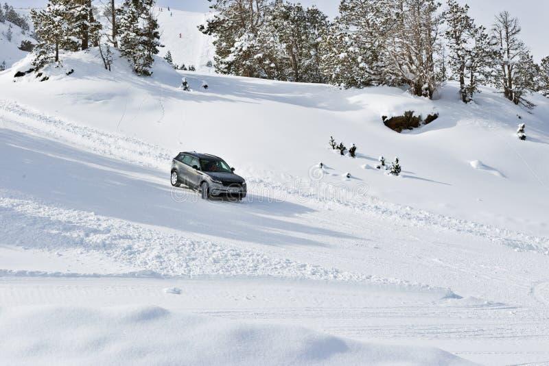 PYRENEES, ANDORRA - 7 DE FEVEREIRO DE 2018: Movimentação do teste Land Rover em uma estrada coberto de neve Fuga do inverno nas m fotografia de stock royalty free