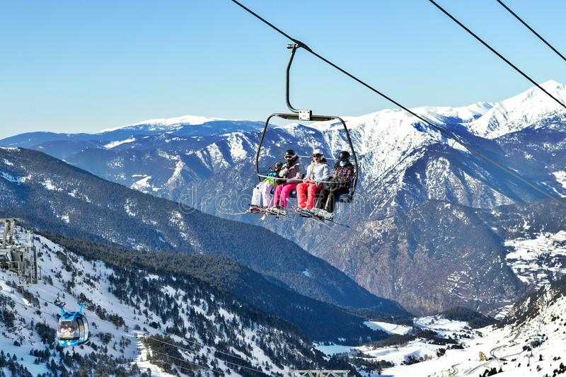 PYRENEES, ANDORRA - FEBRUARY 9, 2017: Skiers on the chair lift o. Ver mountains. Sunny winter day, snow tops and bright clothes stock images