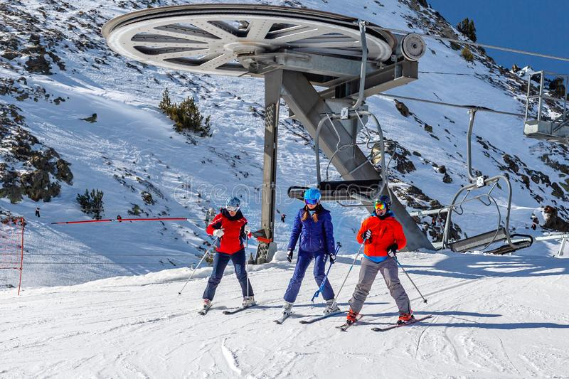 PYRENEES, ANDORRA - FEBRUARY 13, 2019: Three of skiers in colorful clothes walk off the chairlift at the top. Snow covered slope and metal structures in the stock photo