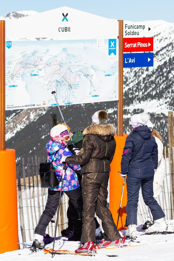 PYRENEES, ANDORRA - FEBRUARY 15, 2019: Unknown tourists are looking at the circuit on the mountainside in a ski resort. Sunny winter day, skier shows stick stock photography
