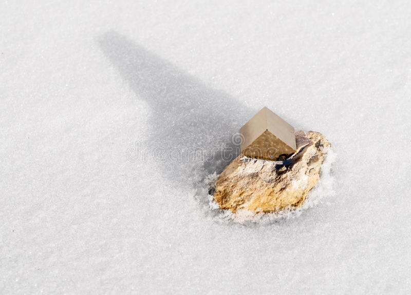 Pyrite crystal. Perfect pyrite crystal on snow royalty free stock photography