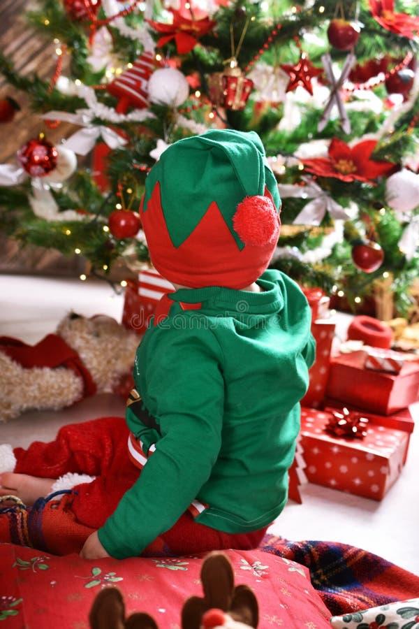 Pys i älvadräkt som tycker om hans första jul royaltyfri foto