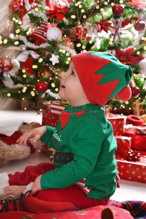 Pys i älvadräkt som tycker om hans första jul royaltyfri fotografi