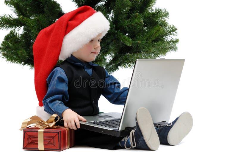 Pys i det Santa Claus locket med en bärbar dator och en julgåva arkivbilder