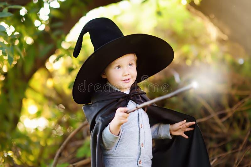 Pys i spetsig hatt och svarta kappan som spelar med trollspöet utomhus liten trollkarl royaltyfria foton