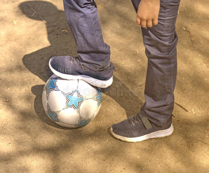 Pys med en boll som spelar fotboll på gatan arkivfoto