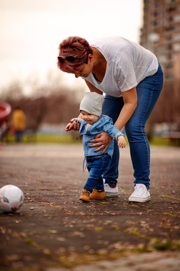 Pys med fotbollbollen som spelar med hans moder i en parkera royaltyfria bilder