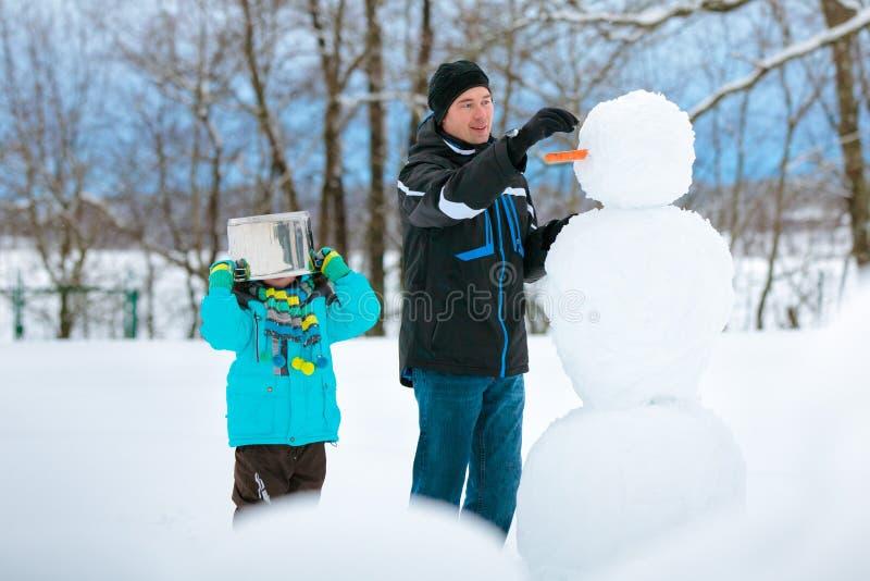 Pys med hans fader som gör en snögubbe royaltyfria bilder