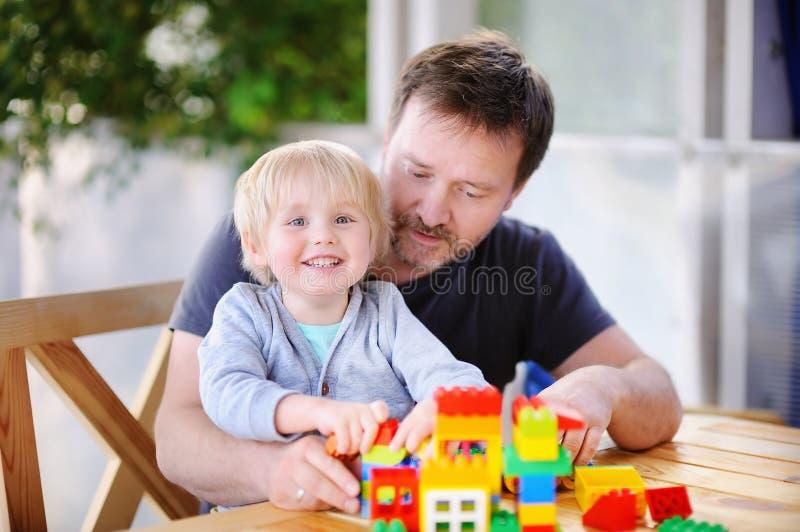 Pys med hans fader som spelar med hemmastadda färgrika plast- kvarter arkivbild