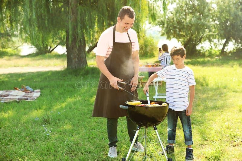 Pys med hans fader som utomhus lagar mat smaklig mat på grillfestgaller royaltyfri fotografi